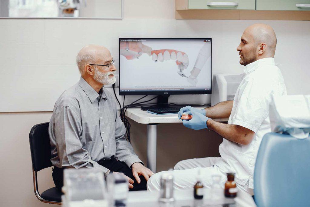 Chirurg stomatolog wyjaśnia pacjentowi przebieg zabiegu.
